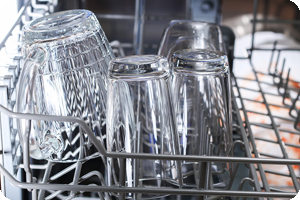Clean glasses being unloaded from dishwasher.