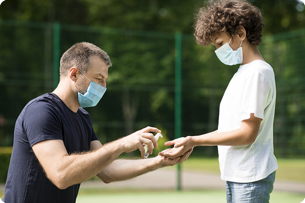 Father applying uScore hand sanitizer to son's hands before sports event