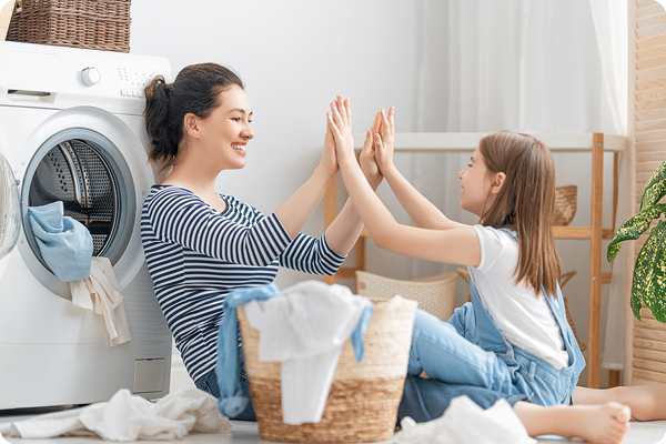 Mother and daughter having fun doing laundry.