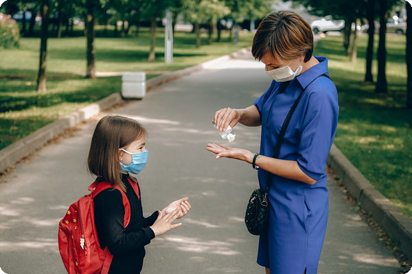 Mother sharing uScore hand sanitizer with school aged daughter