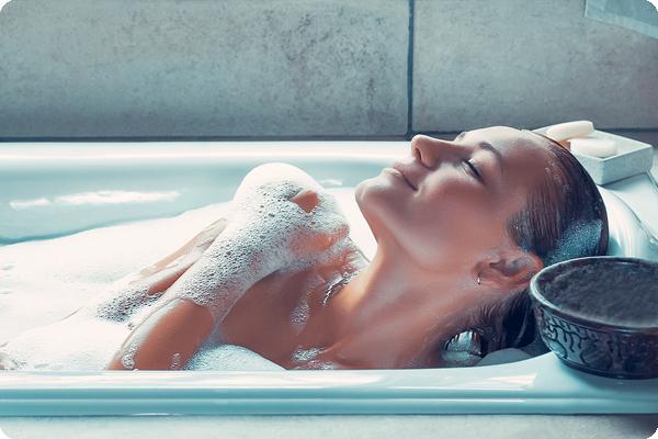 Woman using body wash in bath